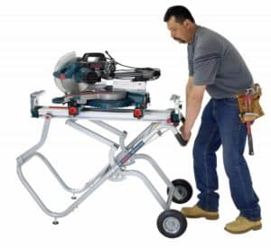 man carrying miter saw on stand