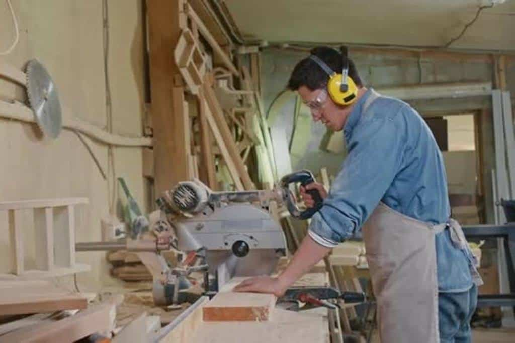 Carpenter Working with Bandsaw in Workshop